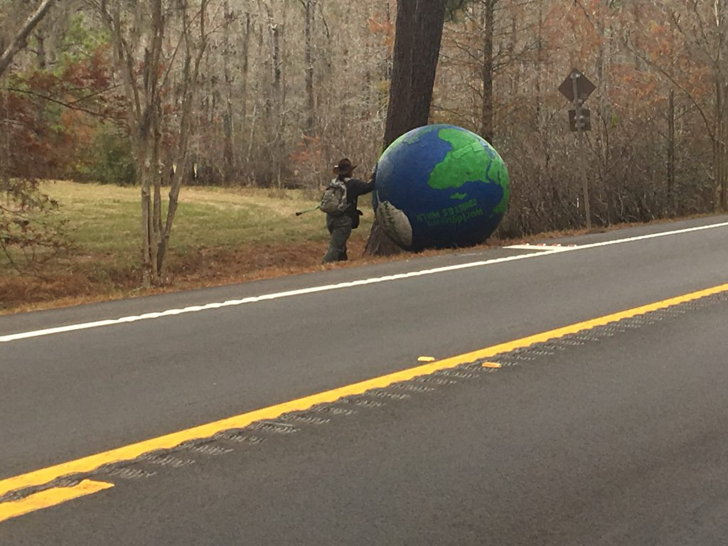 A man rolling a globe along US 90.